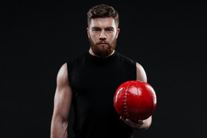 Trainer with ball in hand. serious man isolated dark background