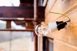 Transparent glass light bulb hangs from a spot on wires on brown wooden board wall of the unfinished house.