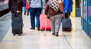 Travellers walk through train station carrying suitcases