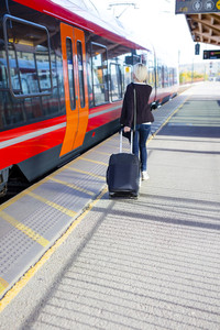 Travling woman at a outdoor train terminal
