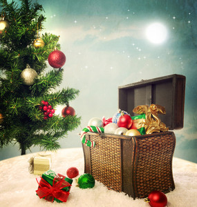 Treasure box filled with Christmas ornaments and presents on snow with Christmas tree