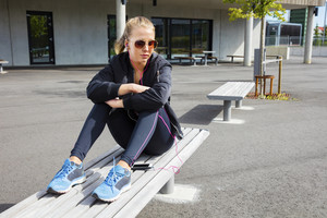 Trendy Woman In Sportswear Listening to Music On Bench