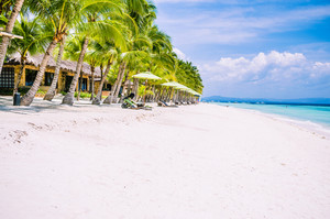 Tropical sandy beach at Panglao Bohol island with Sme Beach chairs under palm trees. Travel Vacation. Philippines