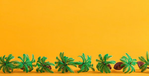 Tropical theme with little palm trees on a yellow background