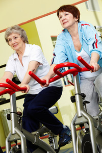 Two active senior women exercising in gym