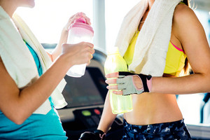 Two attractive fit women in a gym with water bottles and towels during a break, sunny day