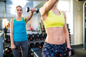 Two attractive fit women in gym working out with weights