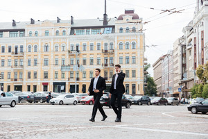 Two attractive young businessmen walking and talking on cell phone in the city