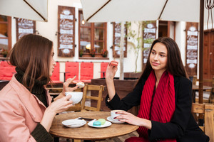 Two attractive young women drinking coffe with french macaroons in outdoor cafe