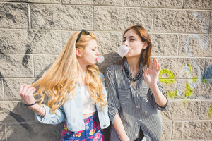 Two beautiful blonde and brunette friends playing with bubblegum in the suburbs - chidhood, carefreeness concept