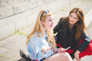 Two beautiful blonde and brunette friends sitting on the floor chatting and having fun using a smartphone - communication, social network, friendship concept - Focus on blonde, overlooking and smiling