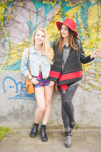Two beautiful blonde and brunette girl having fun posing on a wall in the city suburbs - emancipation, friendship concept