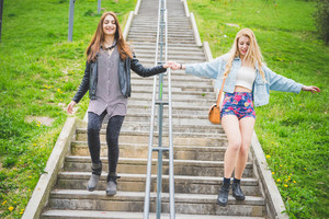 Two beautiful blonde and brunette girl walking down the stairs of a city park - friendship, emancipation  concept