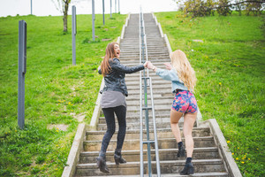 Two beautiful blonde and brunette girl walking on the stairs of a city park - friendship, emancipation concept