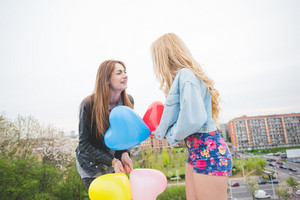 Two beautiful blonde and brunette girls playing with balloons in the city suburbs - childhood, carefreeness concept