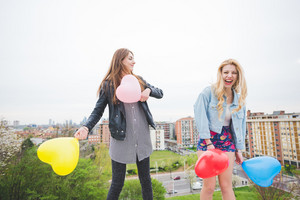 Two beautiful blonde and brunette girls playing with baloons in the city suburbs - childhood, carefreeness concept
