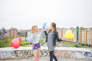 Two beautiful blonde and brunette girls playing with heart shape balloons in the city suburbs - childhood, carefreeness concept