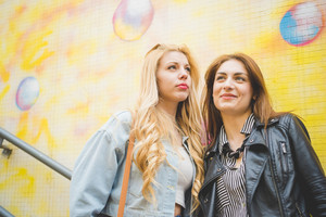 Two beautiful blonde and brunette girls posing and having fun on a colorful subway