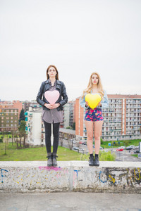 Two beautiful blonde and brunette girls standing on a small wall with city in background, playing with heart shape colorful balloons in the city suburbs - childhood, carefreeness concept