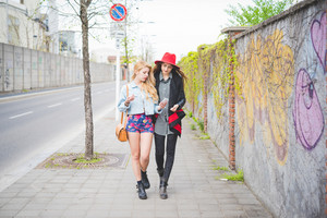 Two beautiful blonde and brunette girls walking down the city using smartphone connected online - technology, social network, communication concept