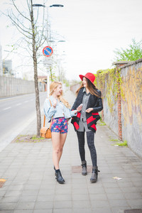 Two beautiful blonde and brunette girls walking down the city using smartphone looking one in each other's eyes laughing - technology, social network, communication concept