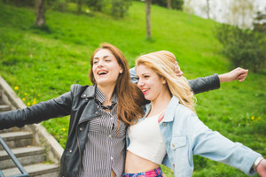 Two beautiful blonde and brunette girls with arms wide open having fun in a city park - friendship, emancipation concept
