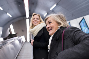 Two beautiful blonde women in black coats and big woolen scarfs standing at the escalator in Vienna subway
