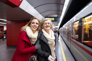 Two beautiful blonde women in winter coats at the underground platform, travelling