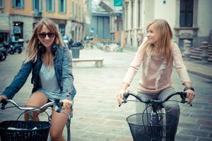 two beautiful blonde women shopping on bike in the city