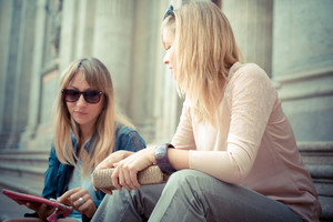 two beautiful blonde women talking in the city