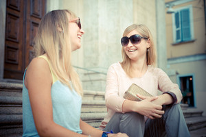 two beautiful blonde women talking in the city