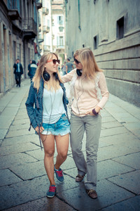 two beautiful blonde women walking and talking in the city