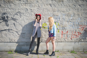 Two beautiful blone and brunette girl having fun posing on a wall in the city suburbs - emancipation, friendship concept