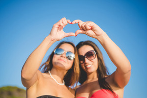 two beautiful friends women sunglasses making heart shape with their hands at the beach in summertime