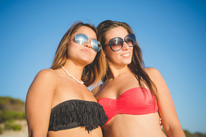 two beautiful friends women with sunglasses sunbathing at the beach in summertime