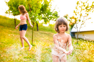 Two beautiful girls at the sprinkler, sunny summer in the garden