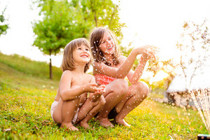 Two beautiful girls crouching at the sprinkler, sunny summer in the garden