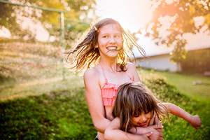 Two beautiful girls having fun outside in the garden, sunny summer back yard