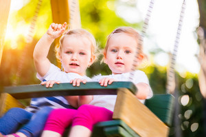 Two beautiful little girls swinging in the park in the summer nature. Friends and sisters.