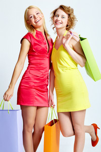 Two beautiful shoppers with paperbags over white background