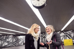 Two beautiful women, mother and daughter, standing at the underground platform, talking.