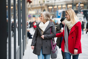 Two beautiful women, mother and daughter, window shopping in historical centre of the city of Vienna, Austria. Winter.