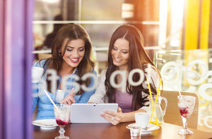 Two beautiful women with tablet in cafe