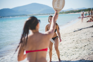 two beautiful young woman having fun  playing with racket at the beach on the foreshore - sport, relax, fun concept