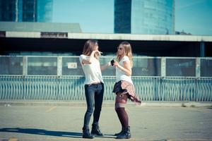 two beautiful young women dancing in the city