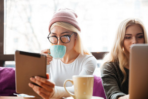 Two beautiful young women drinking coffee and using tablet in cafe