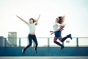 two beautiful young women jumping and dancing in the city