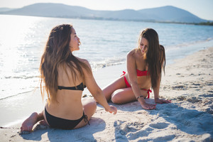 two beautiful young women lying in the sand at the beach in summertime