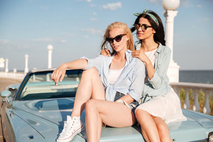 Two beautiful young women sitting on car tohether in summer