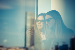 two beautiful young women through glass in the city